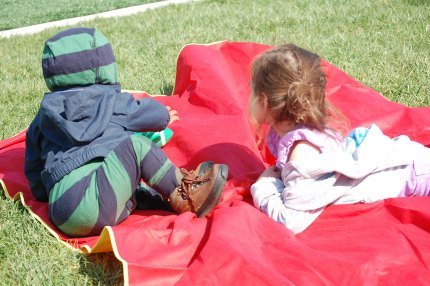 Siblings of soccer players watch the game and lounge on the grass