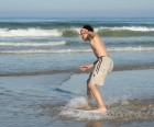 Skimboarding at the edge of the ocean