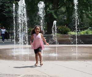 Girl runs through the sprinklers at the East 110th Street Playground