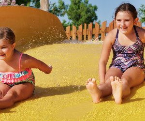 Best Outdoor Water Parks near Chicago: two girl race down water slide