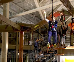 Boy zips down zip line at the Palisades Center