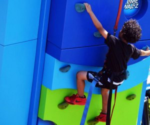 Child scales the climbing wall at Adventures on Governors Island
