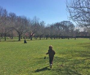 boy running in field brooklyn botanic garden
