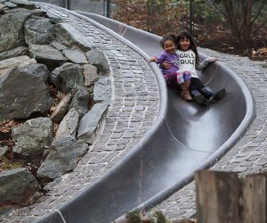 Smiling girls ride the slide at Billy Johnson Playground