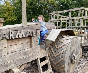girl drives a wooden tractor on a farm
