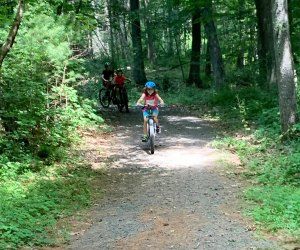 Child riding bike on a path through the woods at Dingmans Campground