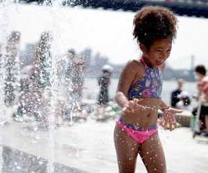 Girl plays in sprinkler at Domino Park