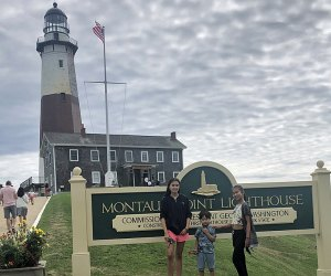 Three kids pose in front of the Montauk Light House