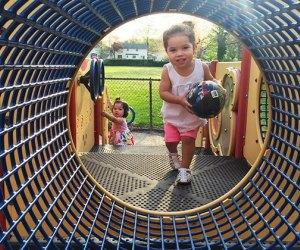 toddler runs through a tunnel at a playground