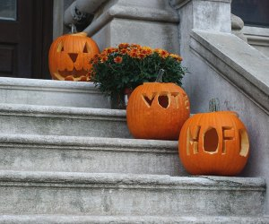 Jack-O-Lanterns and mums decorate a stoop for Halloween