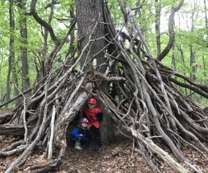 kids hiding in stick structure along a hiking path