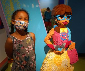 Girl poses with model of Lego Friends character at Legoland Discovery Center at American Dream.