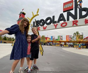 Three kids stand in front of Legoland New York Entrance