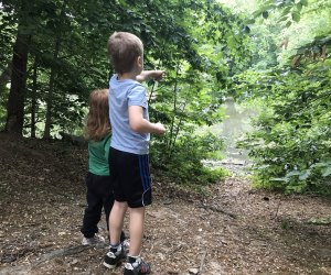 2 kids walk in the woods toward a pond