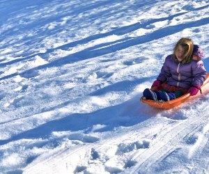 Little girl glides on a sledding hill