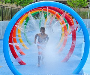 Boy running though tunnel of water spray