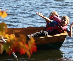 Kids in a canoe with fall foliage in the foreground at Skytop Lodge