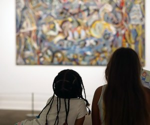 Two girls look at a Jackson Pollock at The Met one of our favorite tourist attractions in NYC