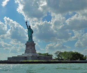 Lady Liberty in New York Harbor on a blue sky day one of our favorite NYC tourist attractions