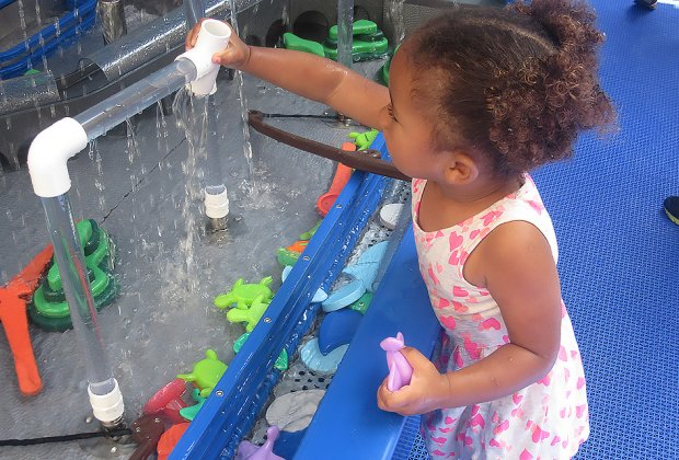 Toddler plays at a water table at CMOM