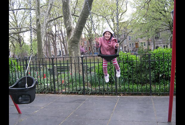 Swinging in Monsignor McGolrick Park Playground