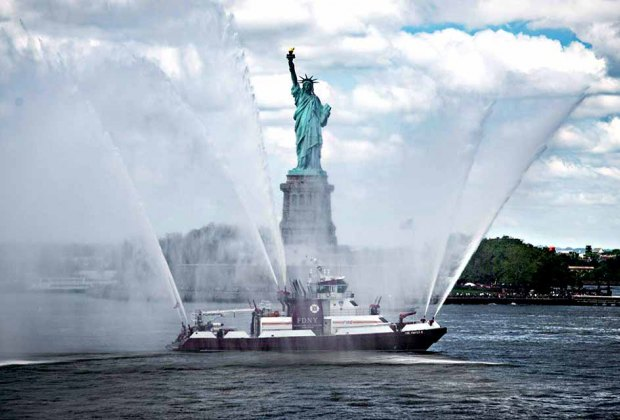 A New York City Fire Department vessel gives a water salute to the State of Liberty for Fleet Week. Photo courtesy of Fleet Week New York
