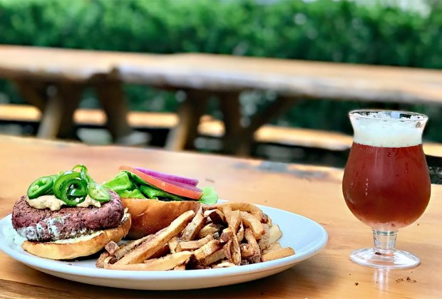 a glass of beer of beer burger and fries on a picnic table on a deck