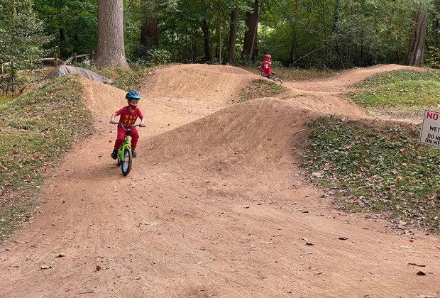 kids riding bikes and jumping on a dirt track