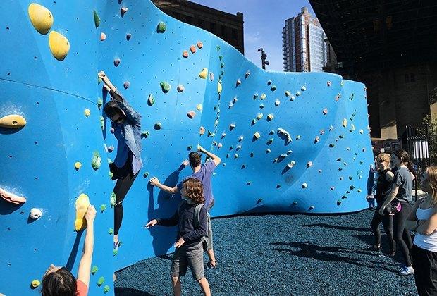 People climbing a rock wall in dumbo