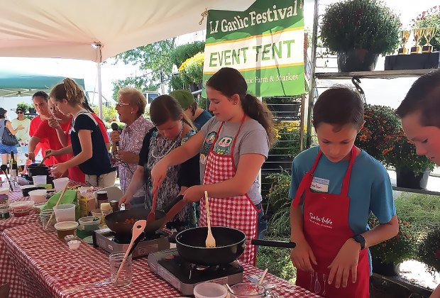 Local children and teens compete in Junior Garlic Iron Chef to create a master garlic-flavored pasta sauce - in front of a live audience - in only half an hour at the Garlic Festival at the Garden Of Eve. Photo courtesy of the farm