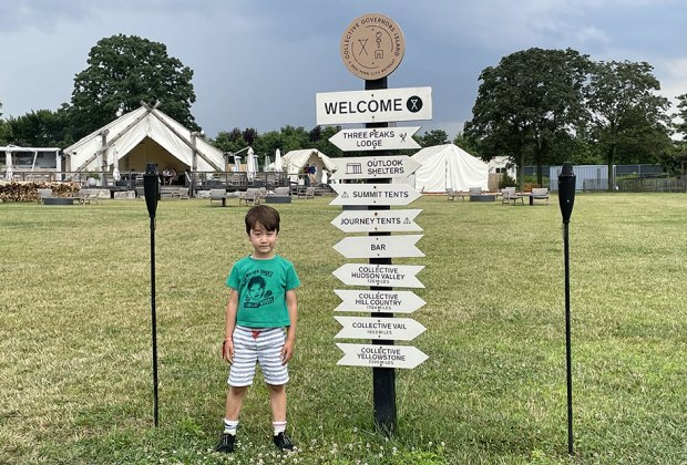 Little boy in front of camp sign at Collective Governors Island