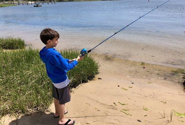 Boy fishing on a Long Island beach