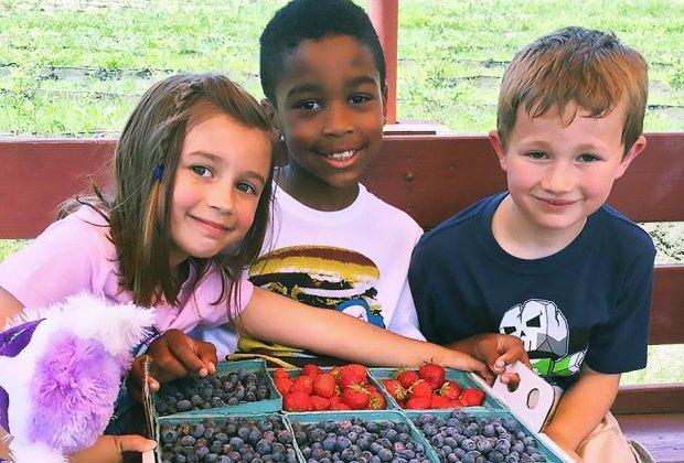 Kids holding bushels of berries at Johnson's Corner Farm