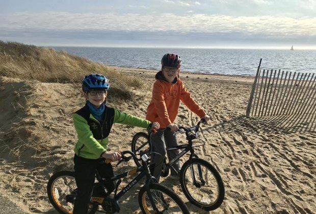 2 boys ride bikes on a sandy beach