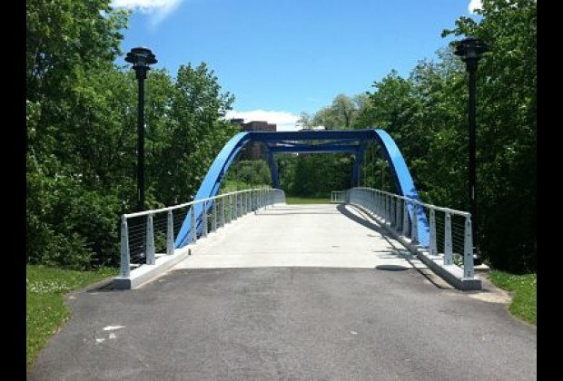 A footbridge over the Bronx River leads to paths and grassy fields