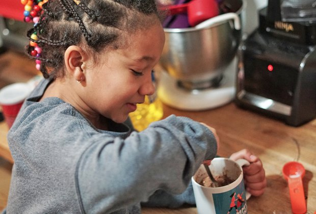 Little girl mixes mug cake