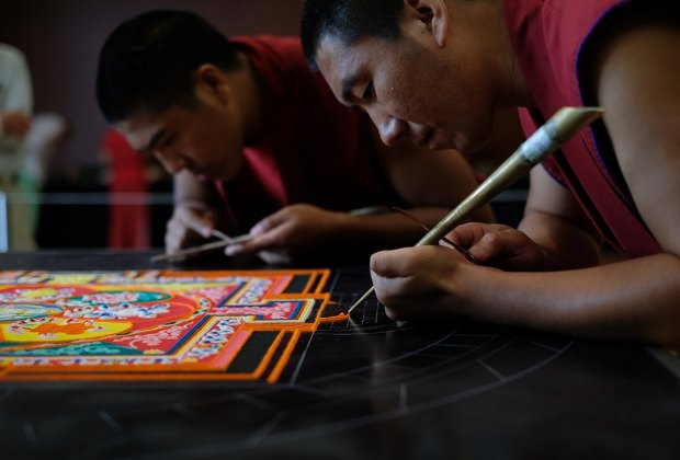 Watch the skill and precision of the Mandala Sand Painting artists at work. Photo courtesy of Asia Society of Texas.