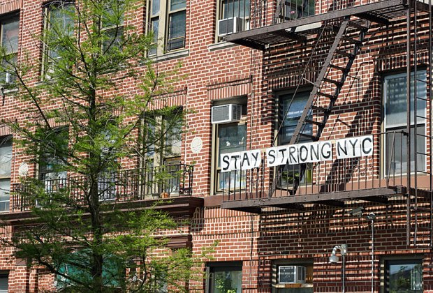 Stay Strong NYC sign hangs from a Harlem fire escape