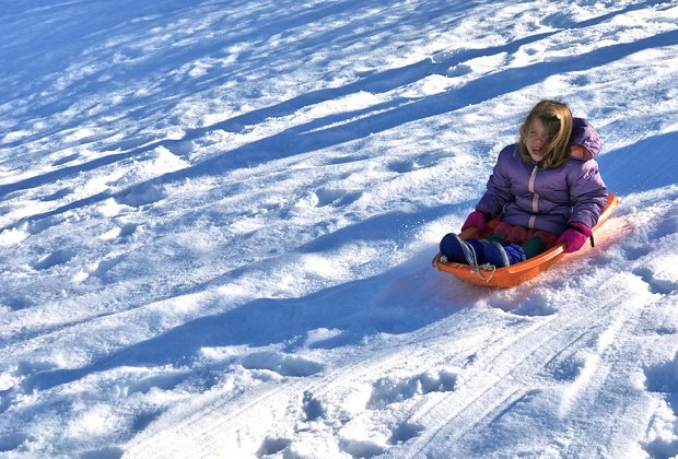 Little girl glides on a sledding hill