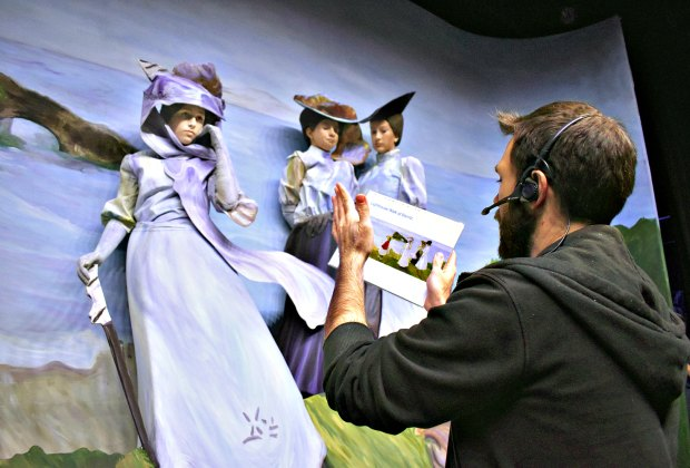 A pageant sculptor helps volunteer cast members into their poses at a rehearsal