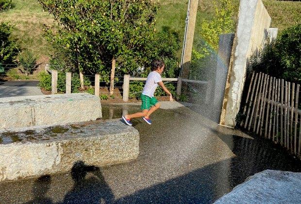 Boy running through Pier 2 Uplands sprinklers