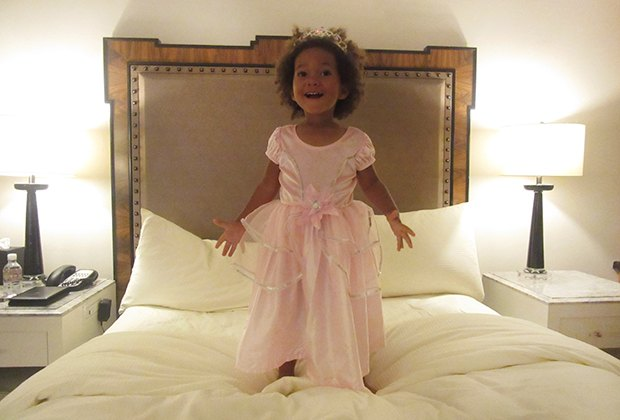 Little girl in princess costume jumping on bed
