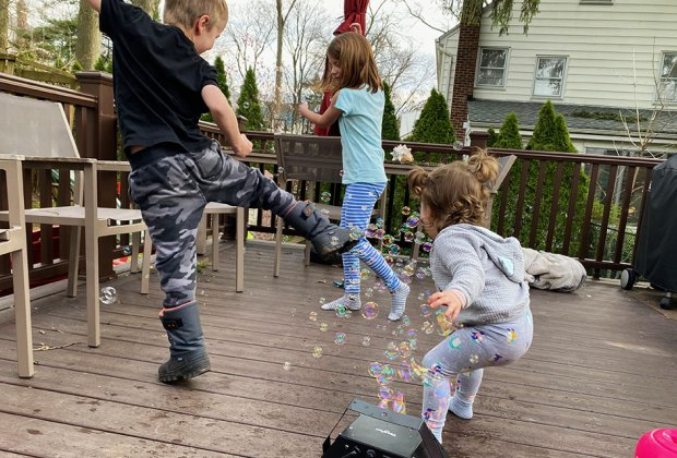 kids playing with bubbles on a deck