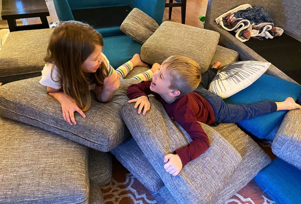 Kids giggle atop a pile of couch cushions
