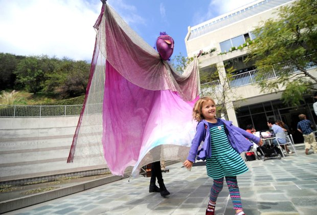 A young Skirball visitor poses with a puppet based on Stravinsky's ballet The Firebird. Photo by Peter Turman