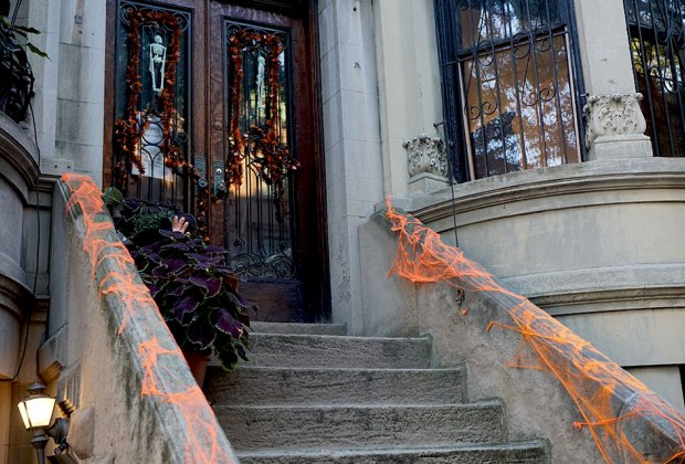 Cobwebs line a stoop and a severed hand reaches from a planter in a Halloween scene