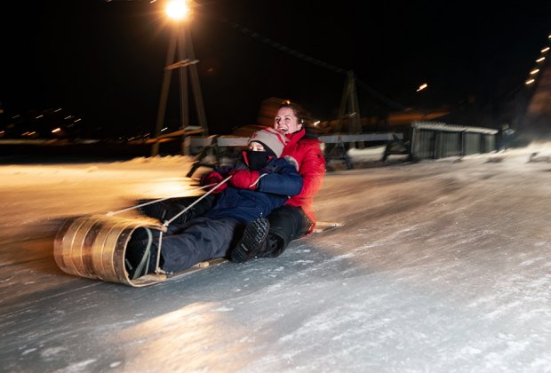 Toboggan Riding on Mirror Lake mother and son riding toboggan Things to Do in Lake Placid on a Winter Vacation Status message